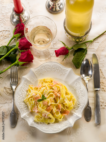 tagliatelle with salmon and cream sauce on luxury table