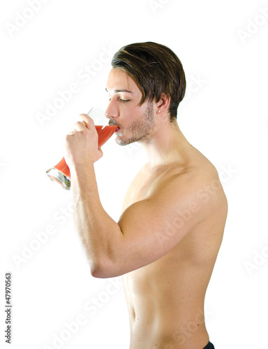 No more beer! Shirtless young man drinking fruit juice