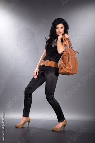 Junges Model in Fashion Mode posiert mit Handtasche