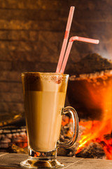 Coffee drink on the background of a burning fireplace