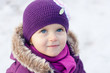 Close-up portrait of a little girl outdoors on a winter day
