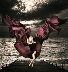 Blonde Woman with Waving Silk at Stormy Sea