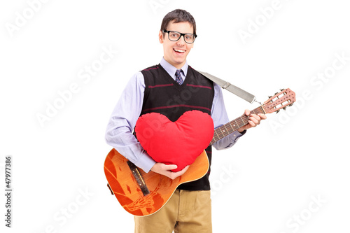 Romantic young man playing an acoustic guitar and holding a red
