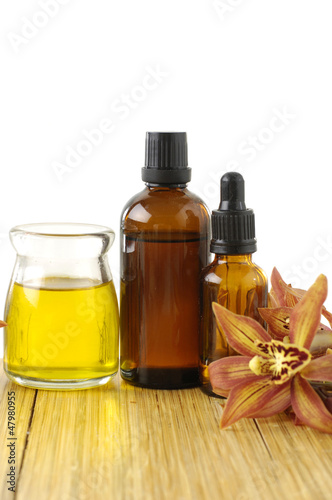 bottle of aromatherapy oil and orchid on wooden board