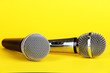 Silver and black microphones on yellow background