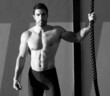 Crossfit gym man holding hand a climbing rope