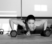 Gymnastikfrau Push-up-Festigkeit Liegestütz mit Hantel