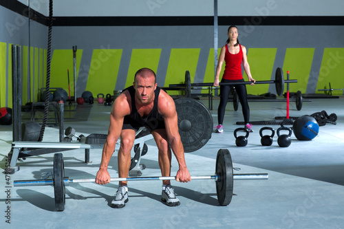 gym with weight lifting bar workout man and woman