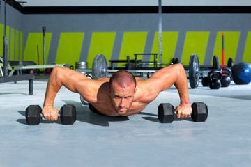 Gym man push-up strength pushup exercise with dumbbell
