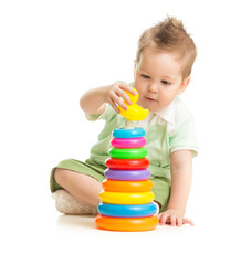 Cute boy playing colorful tower isolated on white