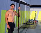 Crossfit man with climbing rope relaxed at gym