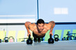 Gym man push-up strength pushup with Kettlebell