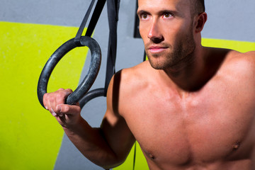 Crossfit dip ring man relaxed after workout at gym dipping