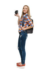 Full length of young female with backpack holding camera