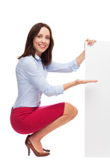 Businesswoman crouching by blank board