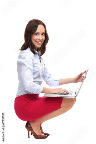 Businesswoman crouching with laptop