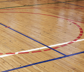 Wooden floor of sports hall with colorful marking lines