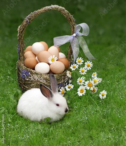 Пасхальная корзина и кролик на зеленой траве