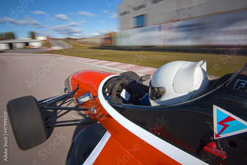 Red bolide driving at high speed in circuit.Camera on board