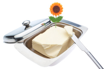 Dish of butter and table knife. On a white background.