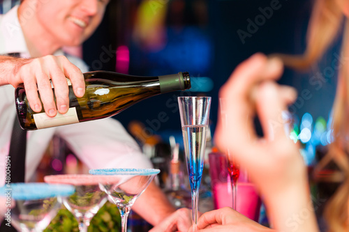 Young woman in club or bar drinking champagne