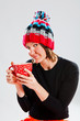 Smiling woman in knitted hat holding cup