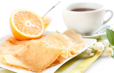 pancakes topped with orange juice and tea