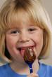 Pequeña niña comiendo crema de chocolate.