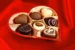 chocolate pralines in golden box on red silk