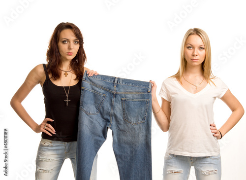 Two sexy friends posing with a pair of jeans