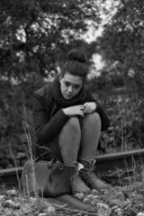 Mujer joven sentada en unas viejas vias de ferrocarril