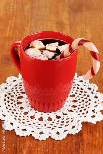Cup of coffee with holiday candy on wooden table close-up
