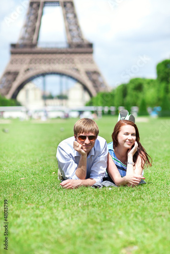 Closeup of happy positive couple laying on the grass near the Ei