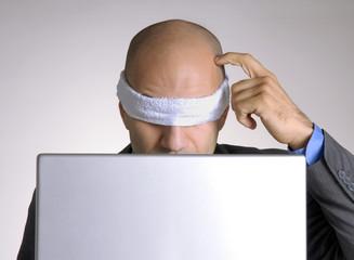 Ejecutivo vendado trabajando en un ordenador,computador.