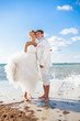Couple hugging on beach posing background of blue sea and sky