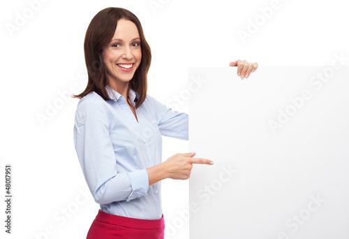 Beautiful woman pointing at blank board