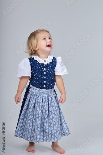 Kind im Dirndl blickt auf ihren Text lachend