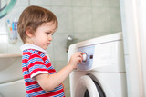 Little baby boy programming washing machine in bathroom