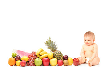 Baby boy sitting next to various fruits and vegetables
