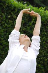 Señora feliz haciendo ejercicios en un jardín.relajada