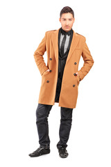 Full length portrait of a handsome smiling man wearing coat