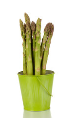 Fresh asparagus in green pail isolated on white.