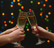 woman hand with glasses of champagne, on garland background.