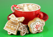 Cup of coffee with Christmas sweetness on green background
