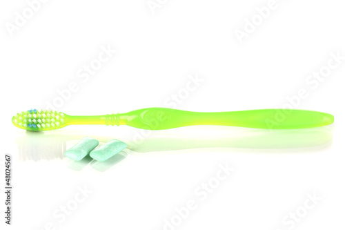 Toothbrush and chewing gum isolated on white