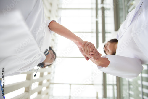 Two young medical doctors shaking hands