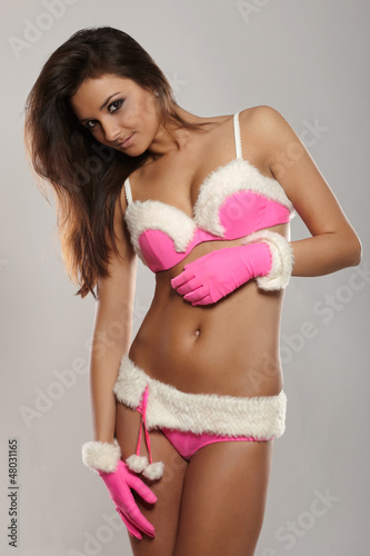 sexy brunette woman dressed as Santa in the studio