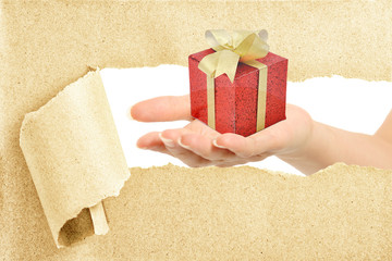 Hand break through paper with gift on hand