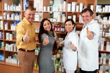 Apotheker-Team mit Kunden halten Daumen hoch