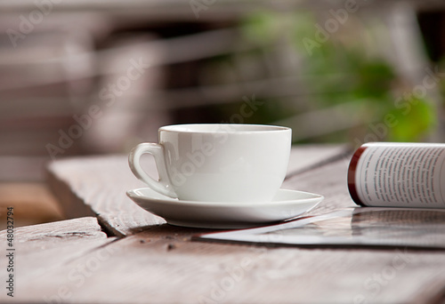 White cup with magazine on the wood table